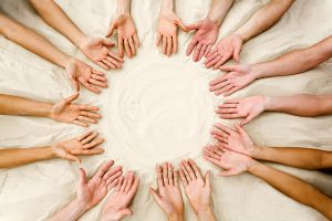 Image of several friendsv hands on sand in the form of circle